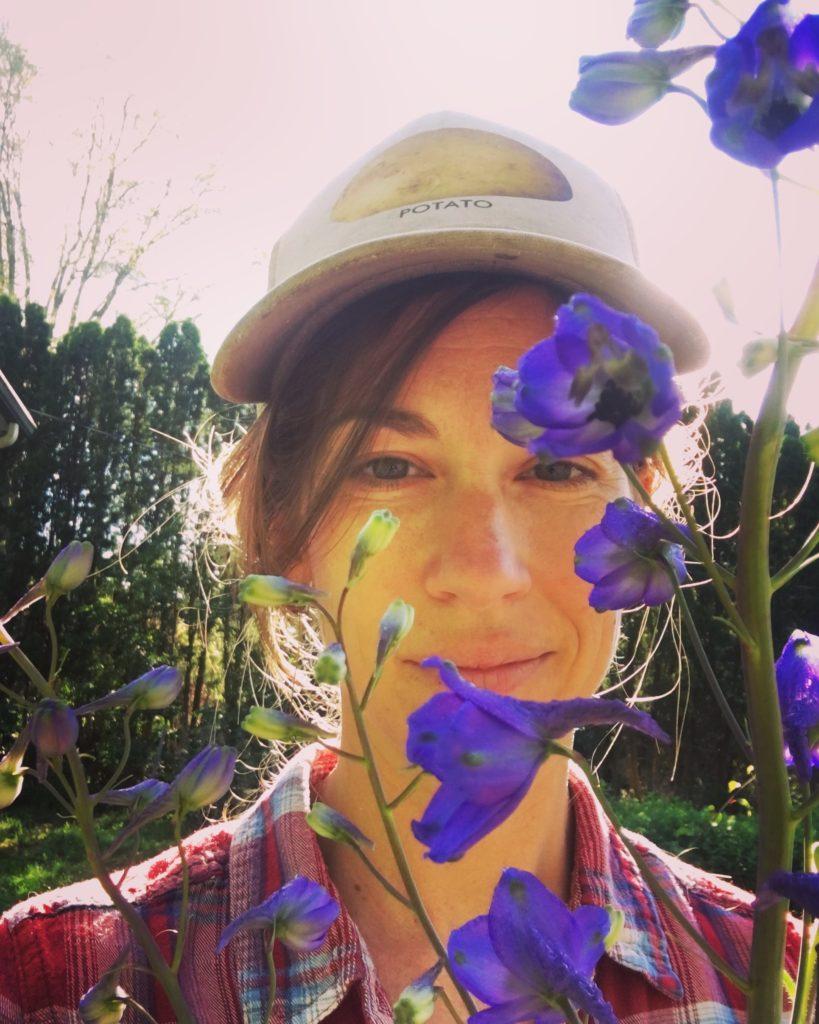 woman posing infront of purple flowers