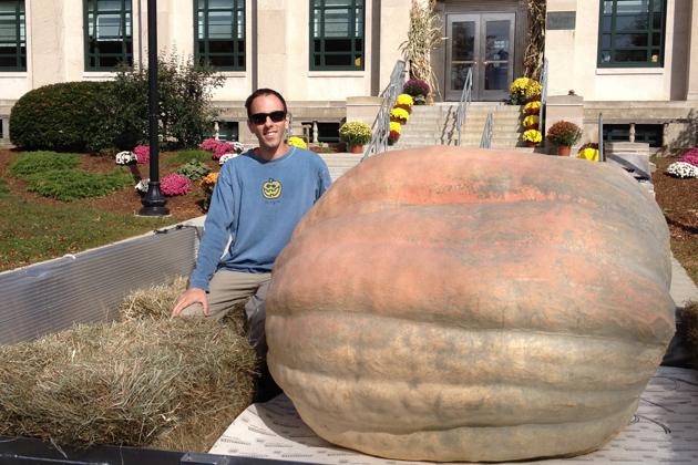 Man next to a giant pumpkin